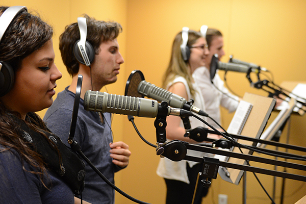 four students in yellow room speaking into recording mics